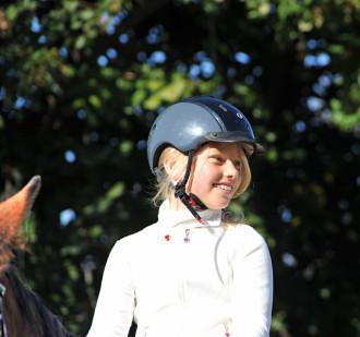 Bestanden! Teilnehmerin des Hufeisen Lehrgangs in den Ferien lächelt mit Reitkappe vom Pferd, Foto des Profils